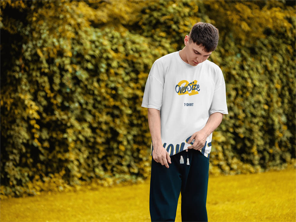 Young man standing in nature with wearing oversize t-shirt with custom printed online buy design